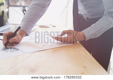 Businessman Analyzing Charts And Graphs With Smartphone.
