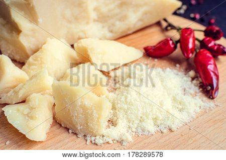 Grated Parmesan cheese with chili pepper on wooden chopping board on dark background. Tasty appetizers. Selective focus.