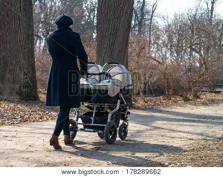 active mom walking in the park with a double twin stroller with two children