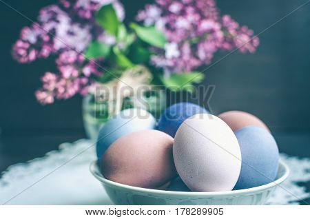 Easter background with handmade painted purple eggs and bouquet of lilac on a dark background. Selective focus.