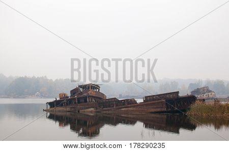 Old rusty sunken ship in water in a foggy day.