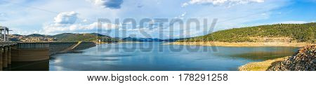 Beautiful Panorama Landscape Of Lake And Dam Surrounded By Hills And Mountains