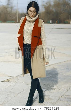 Young beautiful girl model in vest coat of red and beige color and in turtleneck skinned. She also wears dark trousers. The hair of a woman is braided into the tail, and curls weigh in front.