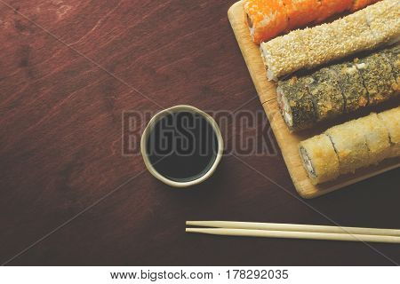 Sushi rolls set served on wooden dish with soy sauce and chopsticks on dark red background, top view with copy space