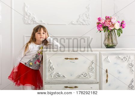 Young girl in a red skirt leaned on the dresser. On the dresser is a bouquet of tulips.
