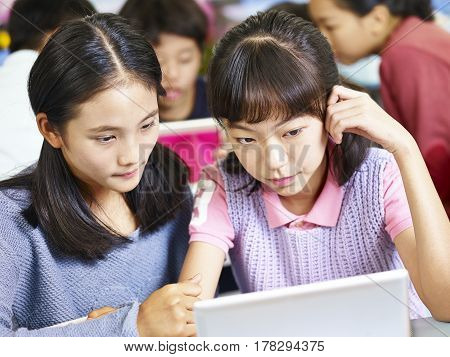 two asian elementary school girls looking at tablet computer thinking hard while working in groups.