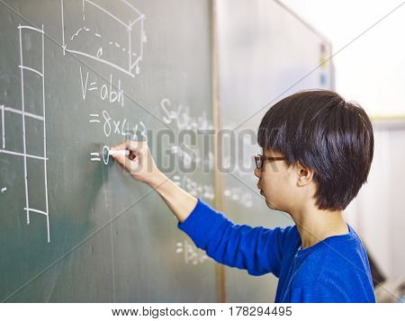 asian grade school student solving a geometry problem on chalkboard in math class.