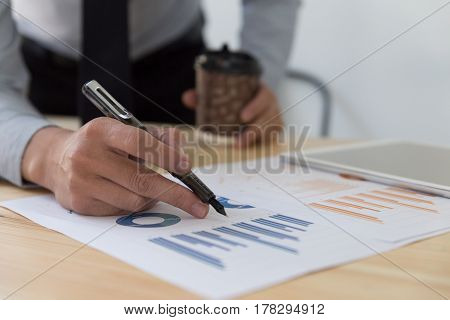 Businessman Holding Coffee Cup And Analyzing Charts And Graphs
