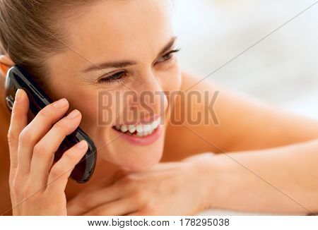 Young Woman Laying On Massage Table And Talking Cell