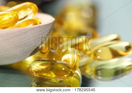 Wooden spoon of pills and oil fish capsules. Omega 3 pills fish oil capsules. Closeup fish oil dietary supplement.