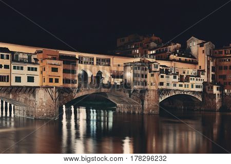 Ponte Vecchio over Arno River in Florence Italy at night.