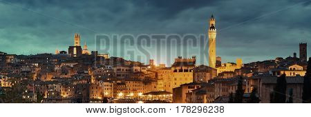 Siena Cathedral and Torre del Mangia Bell Tower with historic buildings. Italy. at night