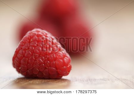 fresh ripe garder raspberries on wood table, closeup photo