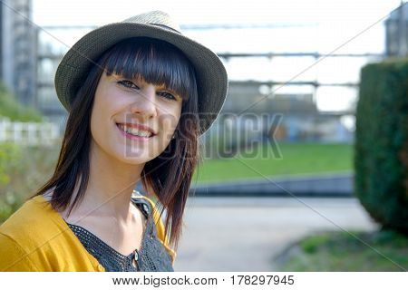 portrait of young brunette girl with summer hat in park outside