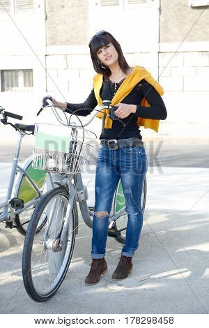 The young woman using public city bicycles