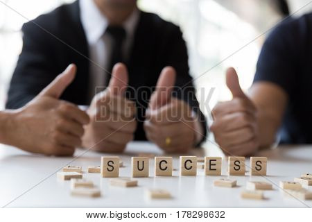 Word 'success' On Wooden Letters With Business Team Group Giving Thumbs Up