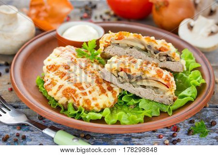 Veal Prince Orloff or French meat - veal chops with mushrooms tomatoes onion cheese and mayonnaise Russian cuisine
