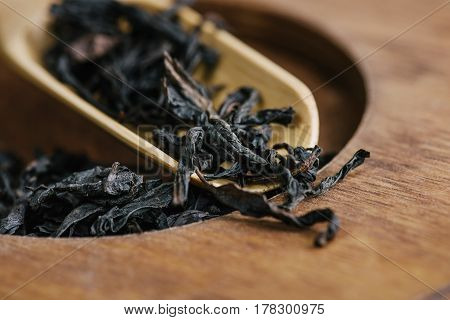 Dry green tea leaves in wooden spoon, selective focus, close-up, horizontal composition. Healthy clean eating lifestyle concept