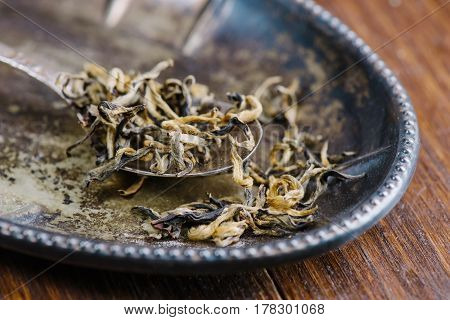 Dry green tea leaves in metal spoon over vintage plate and wooden background, selective focus, close-up, horizontal composition. Healthy clean eating lifestyle concept