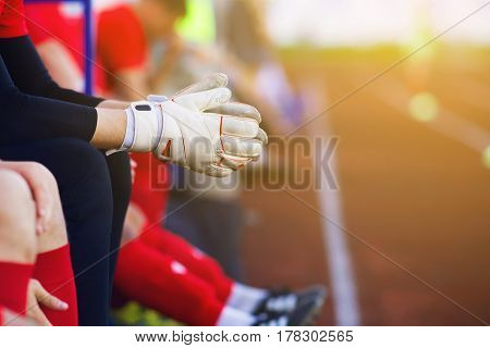 Hands goalkeeper. Gloves closeup. sitting on the bench