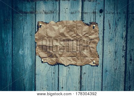 Brown rumpled kraft paper hanging on a blue wooden surface vintage toning
