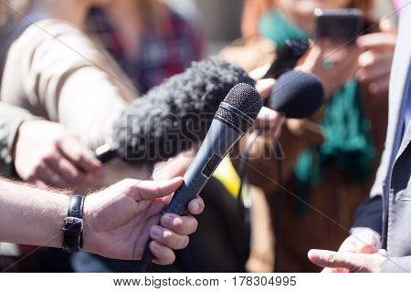 Reporters holding microphones, conducting media interview. News conference.