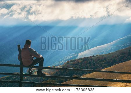 Hiker Sitting On A Wooden Fence