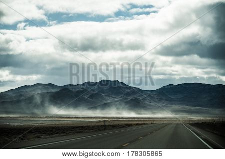 A long empty road perspective leading to the spectacular mountain countryside landscape you can see in America road trip.