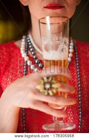 Beautiful woman in the red blouse with a glass of champagne. Close-up.