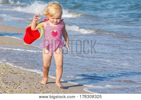 Little happy girl with toy bucket walking on the sea shore.