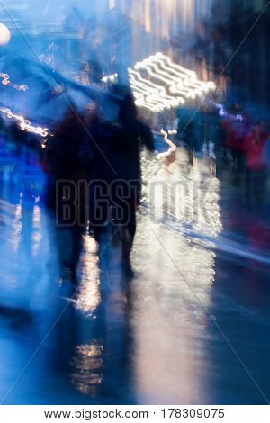 Abstract background in naturale blue tones. People walking down the city street in rainy evening. Light illumination from lanterns and shop windows. Intentional motion blur. Concept of seasons, weather, modern city.