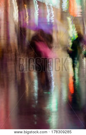 Abstract background of blurred Couple kissing young people in rainy evening, Impressionism style, colorful lighting. Intentional motion blur. Concept of seasons, weather, modern city.