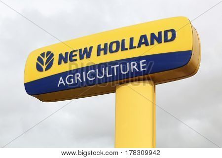 Chateaudin, France - March 19, 2017: New Holland Agriculture logo on a pole. New Holland is a brand agricultural equipment manufactured by CNH Industrial