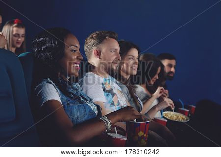 Side view of group of african girl and caucasians couple watching movie in modern cinema hall. Young people eating popcorn and spending free time in cinema.