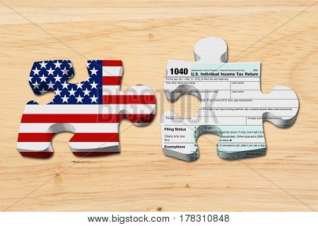 Understanding how to do your taxes Two puzzle pieces with the flag of the USA and a US Federal tax 1040 income tax form on wood 3D Illustration