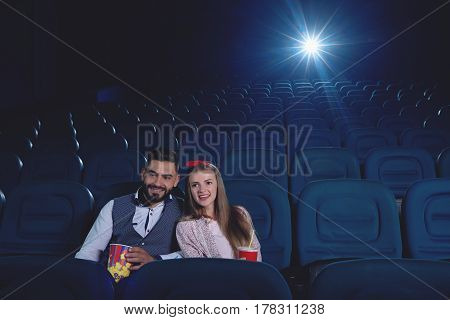 Positive couple arabian man and caucasian woman spending free time in cinema. Two friends embracing and sitting alone in modern cinema hall, watching funny movie.