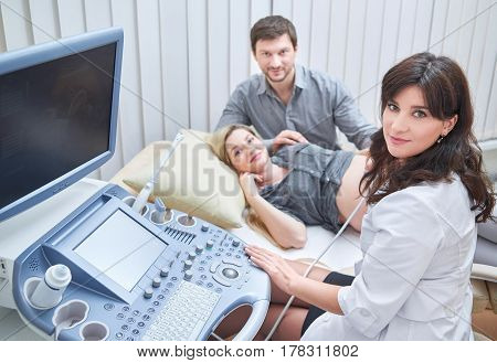 Cheerful female gynecologist and her patient pregnant woman with husband smiling together to the camera while on ultrasound scanning procedure profession medical clinic pregnancy family healthcare.