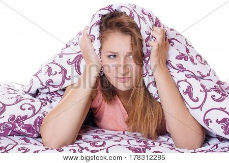 Beautiful young woman suffering from insomnia and covering her head with a pillow.