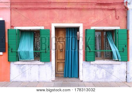 Colorful facade on retro house entrance with open door and windows
