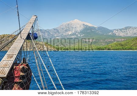 Wooden bowsprit of an old sailing ship against the backdrop of the mountain Tahtali Dagi Turkey.