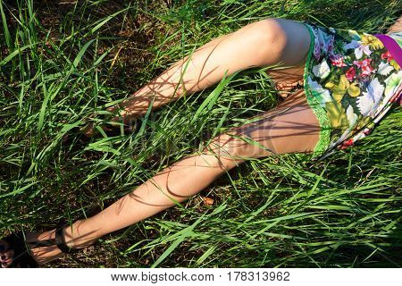 Young woman lying in the grass in a sunny summer day.