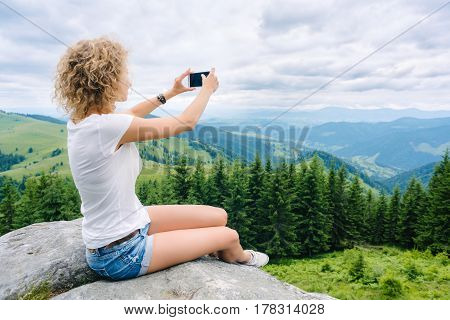 Beautiful woman hiker taking photo with cellphone on mountain top