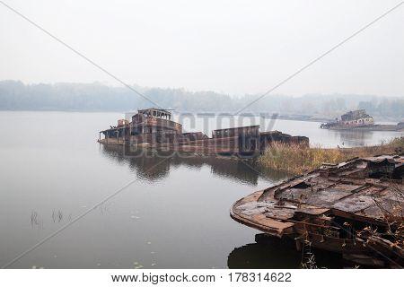 Old rusty sunken ships in water in a foggy day.