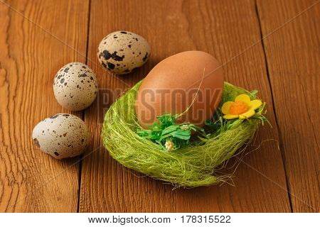 Chicken and quail eggs with a green nest on wooden background