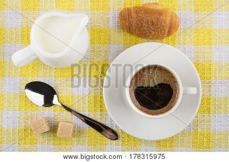 Coffee Cup, Milk Jug, Croissant, Sugar And Spoon On Napkin