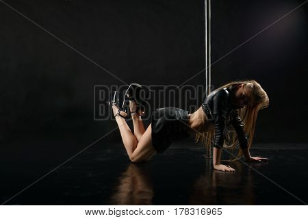 Sexy long haired blonde dresses in black leather jacket, mini skirt and high heel shoes posing by the pylon in a graceful pose staying on her knees studio shot