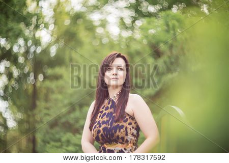 Portrait of a sexy sensual beautiful brunette girl with long hair in leopard yellow-black dress walking in the park.