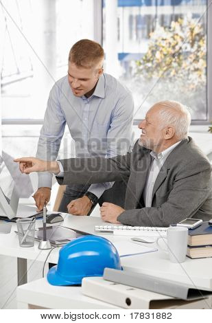 Senior and junior designers discussing work together in office, senior man pointing at screen.?