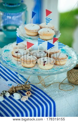 A beautiful composition of muffins with flags twine cockleshells lying on a table