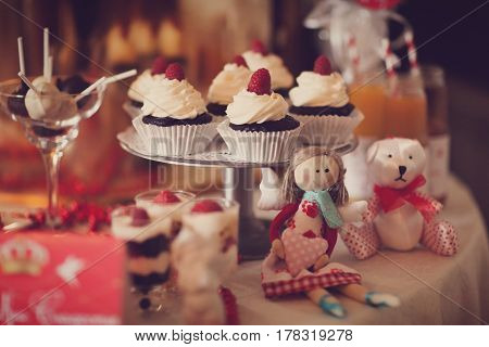 Children's festive table with toys and sweets-different cakes sweets biscuits